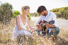 Handsome man serenading his girlfriend with guitar Royalty Free Stock Photography