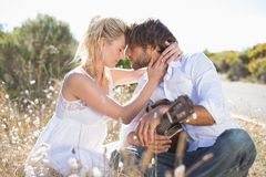 Handsome man serenading his girlfriend with guitar Stock Images