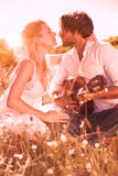 Handsome man serenading his girlfriend with guitar Stock Photography