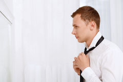 Handsome man seriously fixing his tie Royalty Free Stock Image