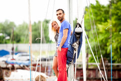 Handsome man and sexy girl standing on yacht at seaport Stock Images