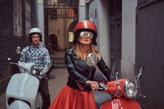 Handsome man and a stylish girl are walking with retro Italian scooters along the old streets of the city. stock image