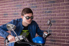 Handsome Man in Shades and Jacket on a Motorbike Royalty Free Stock Images