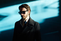 Handsome Man in Shadow and Light. Portrait of handsome man wearing sunglasses and black coat in bright sunlight against blue background, looking away from camera Stock Photo