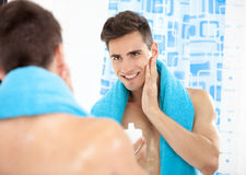 Handsome man after shave. Portrait of a young man in the bathroom applying after shave stock image