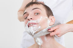 Handsome man shaves a woman with a knife Stock Image