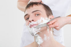 Handsome man shaves a woman with a knife Royalty Free Stock Image