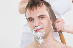 Handsome man shaves a woman with a knife Royalty Free Stock Photos