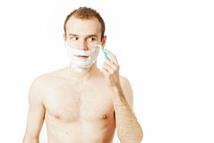 Handsome man shaving. Portrait of a young handsome man shaving as part of his morning routine Stock Photo