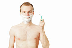 Handsome man shaving. Portrait of a young handsome man shaving as part of his morning routine Royalty Free Stock Images