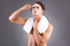 The handsome man shaving against dark background Royalty Free Stock Photography