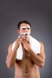 The handsome man shaving against dark background Royalty Free Stock Image