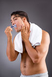 The handsome man shaving against dark background Royalty Free Stock Images