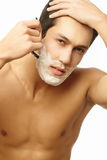 Handsome man shaving as part of morning routine Stock Photo