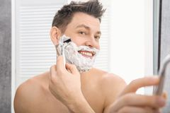 Handsome man shaving. In bathroom royalty free stock photography