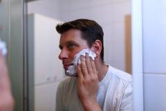 Handsome man shaving in bathroom. Happy handsome man shaving in bathroom Stock Image
