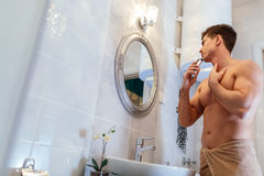Handsome man shaving in bathroom. Reflection in mirror Royalty Free Stock Photos