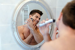 Handsome man shaving in bathroom. Reflection in mirror Stock Photo