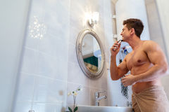 Handsome man shaving in bathroom. Reflection in mirror Royalty Free Stock Photo