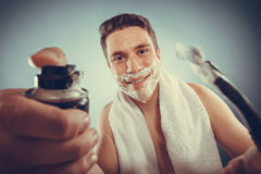 Handsome man with shaving cream foam can and razor Stock Image