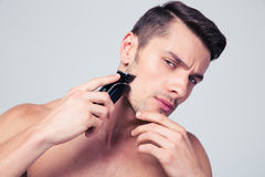 Handsome man shaving with electric razor Royalty Free Stock Photography