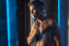 Handsome Man Shaving Face In Bathroom. Facial Hair Grooming Royalty Free Stock Photo