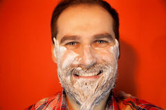Handsome man with shaving foam on his face and razor Stock Image