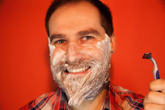 Handsome man with shaving foam on his face and razor Royalty Free Stock Image