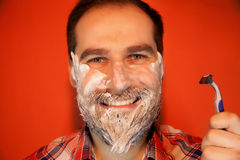 Handsome man with shaving foam on his face and razor Royalty Free Stock Photo