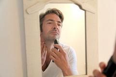 Handsome man shaving in front of mirror stock photo