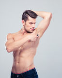 Handsome man shaving his armpit Stock Photo