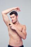 Handsome man shaving his armpit Stock Image