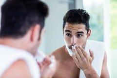 Handsome man shaving his beard. In bathroom Stock Photography
