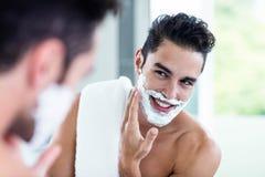 Handsome man shaving his beard. In bathroom Royalty Free Stock Photos