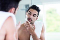 Handsome man shaving his beard. In bathroom Stock Image