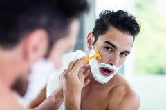 Handsome man shaving his beard. In bathroom Stock Photos