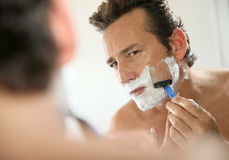 Handsome man shaving. Mature handsome man shaving in front of mirror royalty free stock image
