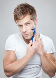 Handsome man shaving. Portrait of a handsome man shaving stock photography