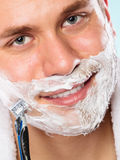 Handsome man shaving with razor Royalty Free Stock Image
