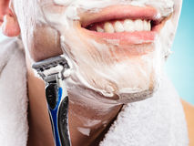 Handsome man shaving with razor Stock Images