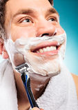 Handsome man shaving with razor Royalty Free Stock Photos