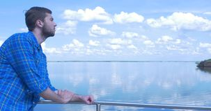 Handsome man of the ship and looking to the city.Man ,stylish boy,blue shirt,pretty boy,attractive,spring vacations. Ferry,casual wear,man at the sea,bracelets stock footage