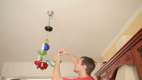 A handsome man shirt changes a light bulb to a crystal lamp stock footage