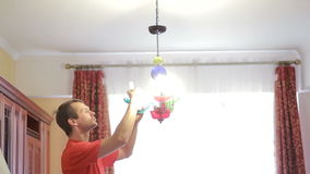 A handsome man shirt changes a light bulb to a crystal lamp stock video footage