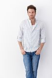 Handsome man in shirt and jeans. Handsome young man standing over white background, wearing shirt and jeans royalty free stock images