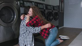 Handsome man in shirt making proposal in laundry to red curly hair woman. She says yes stock video