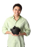Handsome man in shirt with piggy bank. Young good looking student wearing a green shirt with black pants and a piggy bank. White background Stock Images