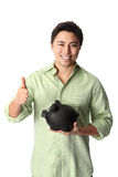 Handsome man in shirt with piggy bank. Young good looking student wearing a green shirt with black pants and a piggy bank. White background Royalty Free Stock Image