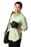 Handsome man in shirt with piggy bank. Young good looking student wearing a green shirt with black pants and a piggy bank. White background Royalty Free Stock Photo