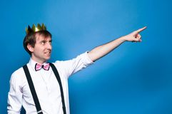 Man in shirt, suspender, bow tie and golden crown, smiling, looking away and ponting with finger into distance on blue background royalty free stock photo